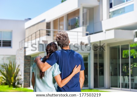 couple embracing in front of new big modern house, outdoor rear view back looking at their dream home - stock photo