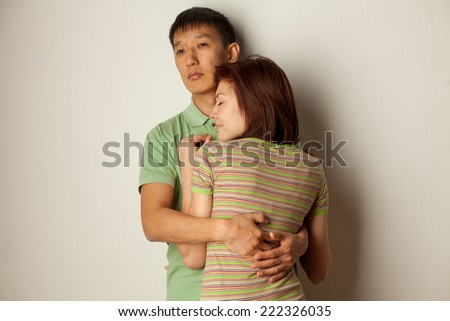 couple embracing in studio against a wall - stock photo