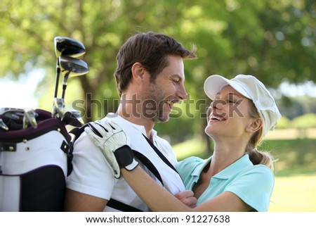 Couple embracing on the golf course - stock photo