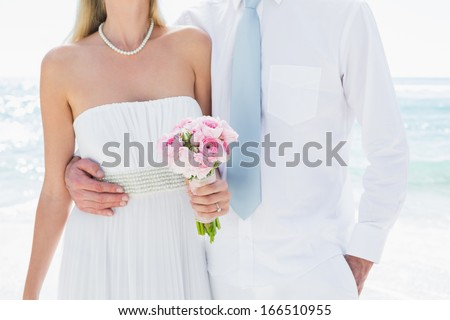 Couple embracing on their wedding day at the beach - stock photo