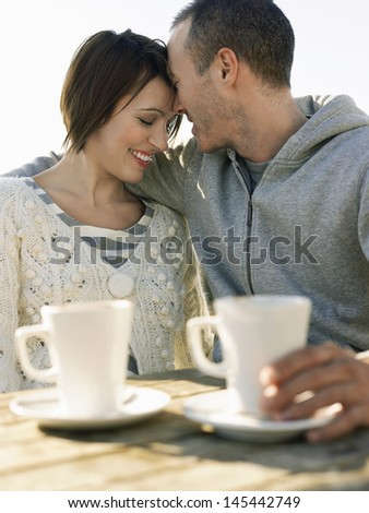 Couple embracing while sitting at the outdoor caf���© table - stock photo