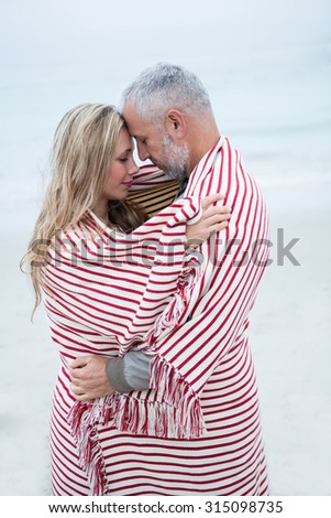 Couple embracing while wrapped in a beach towel by the sea - stock photo