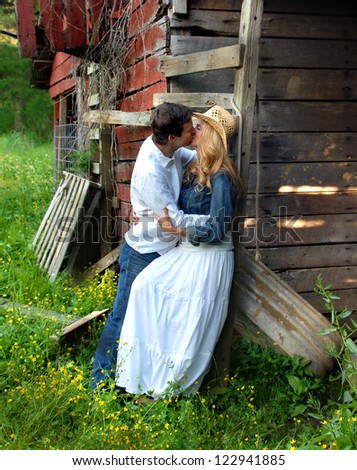 Couple enjoy a romantic kiss against a rustic and secluded setting.  A red, wooden, weathered barn supports them in this rural setting. - stock photo