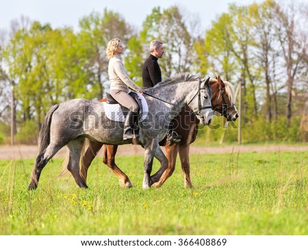 Couple enjoy riding horses in summer meadow. - stock photo