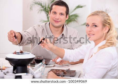 Couple enjoying a chocolate fondue - stock photo