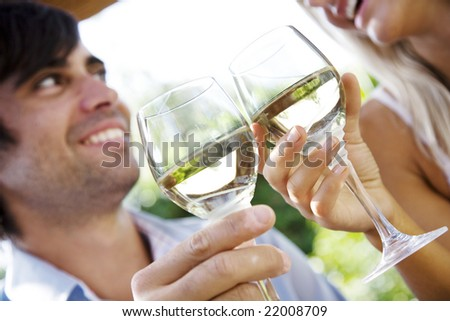 couple enjoying a glass of whitewine in the garden - stock photo