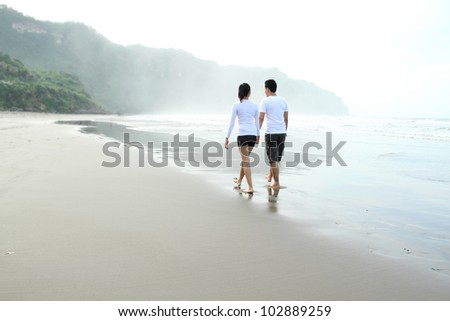 Couple enjoying a summer vacation on the beach - stock photo