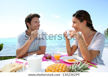 Couple enjoying breakfast in resort - stock photo