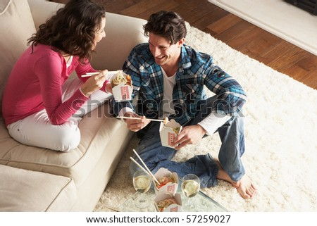 Couple Enjoying Chinese Takeaway Meal At Home - stock photo