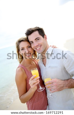Couple enjoying cocktail on caribbean beach - stock photo