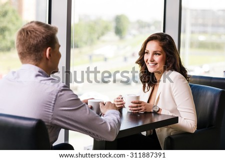 Couple enjoying coffee and talking in cafe - stock photo