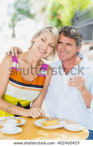 Couple enjoying coffee with food at cafe - stock photo