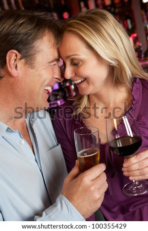 Couple Enjoying Drink Together In Bar - stock photo