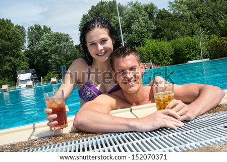 Couple enjoying drinks in their holidays at swimming pool