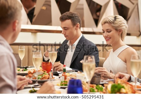 Couple enjoying food at dinner with friends
