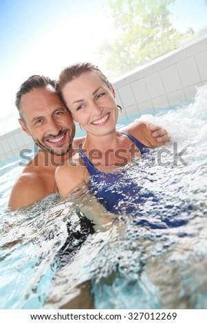 Couple enjoying hot tub bath in spa center - stock photo