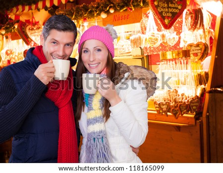 couple enjoying hot wine punch claret on christmas market - stock photo