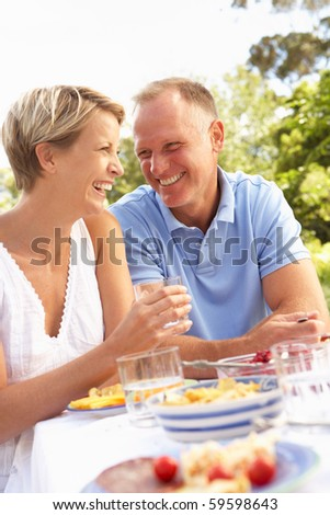 Couple Enjoying Meal In Garden - stock photo