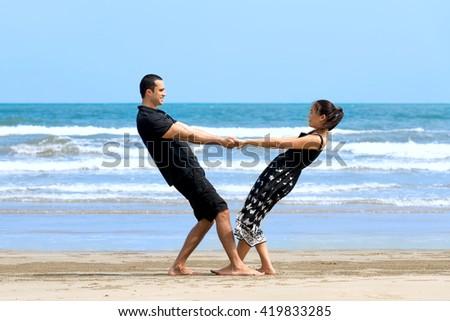Couple enjoying on beach.Young happy interracial couple enjoying on beach  and smiling to each other. Asian woman,Caucasian man   - stock photo