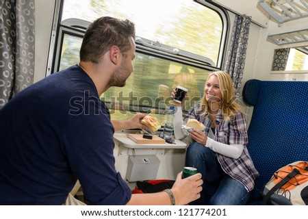 Couple enjoying sandwiches traveling with train smiling woman man vacation - stock photo
