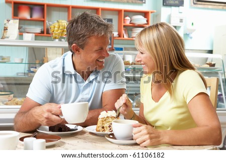 Couple Enjoying Slice Of Cake And Coffee In Cafe - stock photo