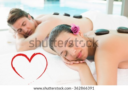 Couple enjoying stone massage at health farm against heart - stock photo