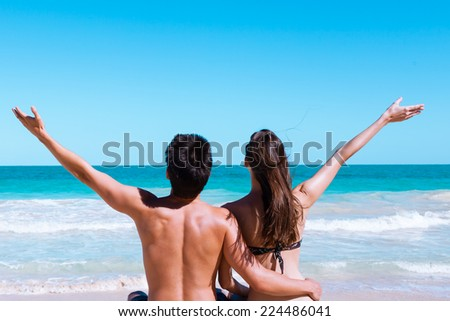 Couple enjoying sunny day at the beach - stock photo