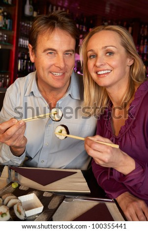 Couple Enjoying Sushi In Restaurant - stock photo