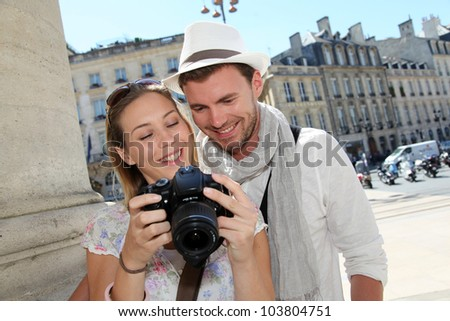 Couple enjoying taking pictures while visiting city - stock photo