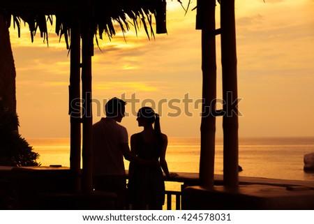 Couple enjoying the sunset in a exotic island hotel setting.  - stock photo