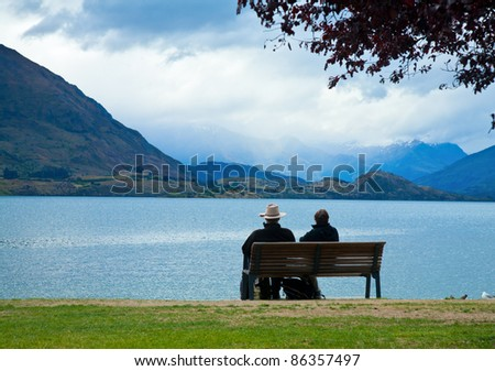 Couple enjoying the view of Lake Wanaka in  New Zealand on an overcast day - stock photo