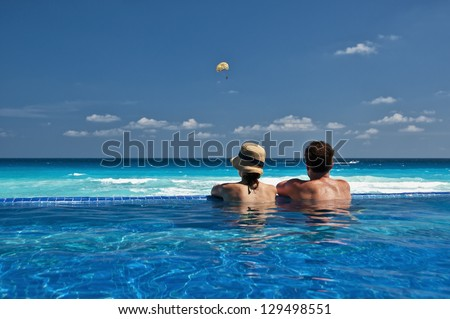 couple enjoying the view of the Caribbean from an infinity pool - stock photo