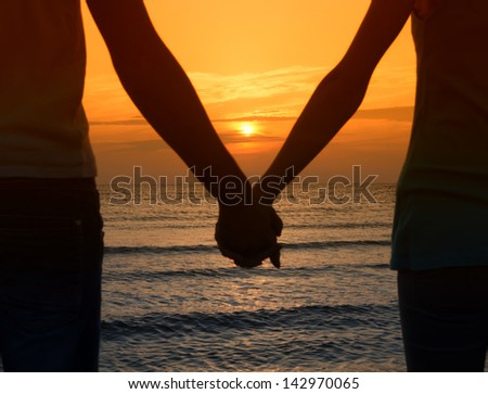 Couple enjoying their time at the sunrise on the beach, couple holding their hands in a romantic scene - stock photo