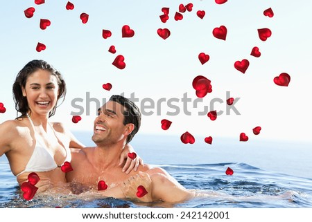 Couple enjoying time together in the pool against valentines heart design - stock photo