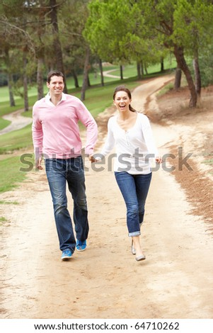 Couple enjoying walk in park - stock photo