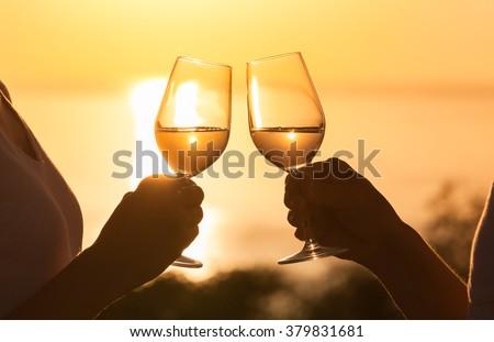 Couple enjoying wine against a beautiful sunset.  - stock photo