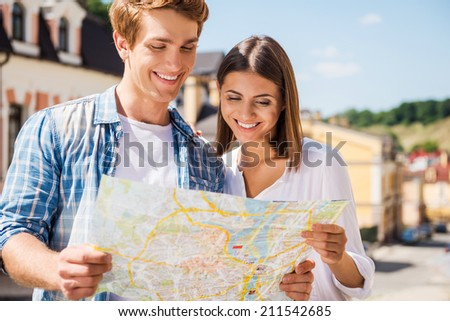 Couple examining map. Happy young tourist couple examining map together while standing outdoors - stock photo