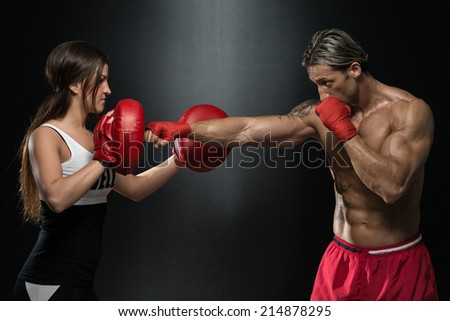 Couple Exercising Punching - Bodybuilding Couple Posing With Boxing Gloves On Black Background