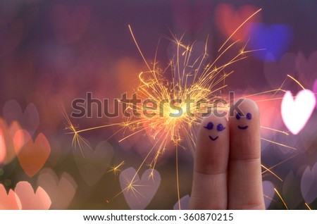 couple face painted at finger on Electric sparklers with heart bokeh background,happy couple concept, Love and valentine concept - stock photo