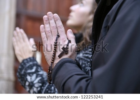 Couple facing the church door, praying with rosary in hand - stock photo