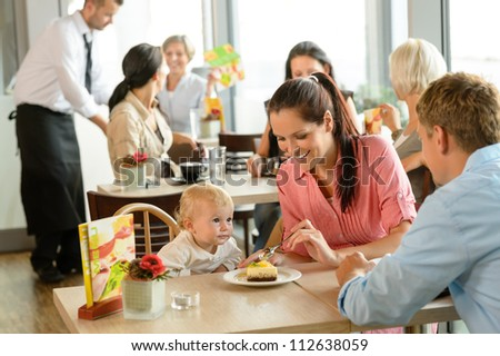 Couple feeding their child cake at cafe restaurant woman man - stock photo