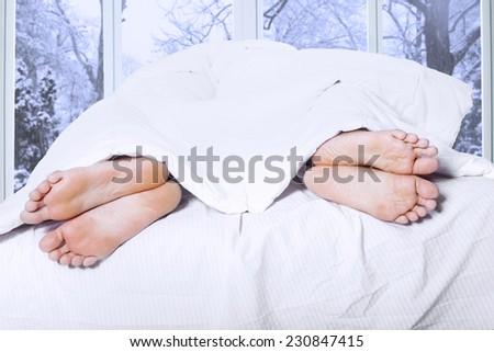 Couple feet sleeping separately on the bedroom, symbolizing couple having family problem - stock photo