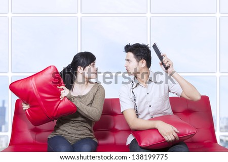 Couple fight on red sofa in apartment - stock photo