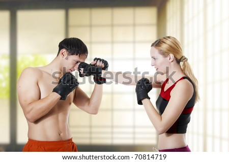 Couple fight. Young adult cute woman fighter punching man, studio shot - stock photo