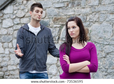 Couple fighting. A young man is trying to have a conversation, while he's been ignored by his girlfriend - stock photo
