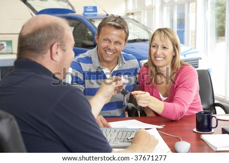 Couple filling in paperwork in car showroom - stock photo