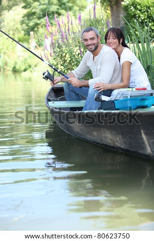 Couple fishing in a boat on a river - stock photo
