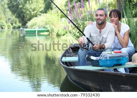 Couple fishing in a small boat on a river - stock photo