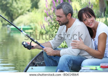 Couple fishing on a river - stock photo
