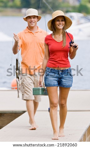 Couple fishing on pier - stock photo
